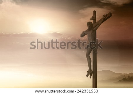 Silhouette Jesus and the cross over blurred sunset background - stock photo