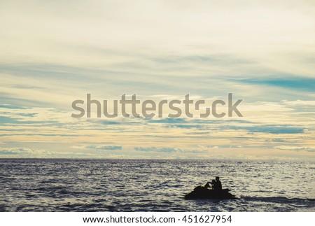Silhouette jet ski on the sea in sunset - stock photo
