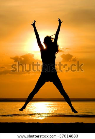 Silhouette jumping women on sundown