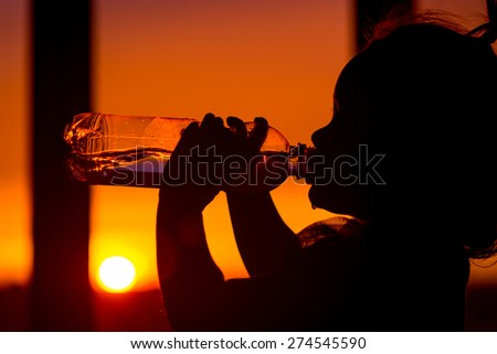 silhouette  kid drinking pure fresh water in nature