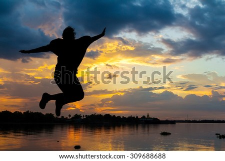 Silhouette lady jumping happy beside the river at sunset