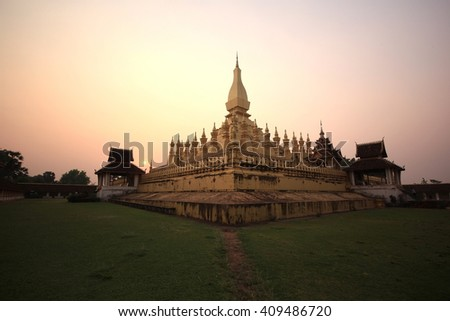 silhouette: Laos travel landmark, golden pagoda wat Phra That Luang in Vientiane. Buddhist temple. Famous tourist destination in Asia. APR 7 2016, popular  - stock photo