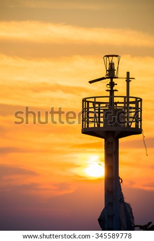 Silhouette lighthouse searchlight beam near ocean at sunset - stock photo