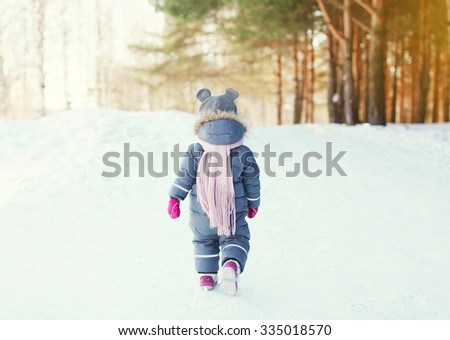 Silhouette little child walking in forest on a winter day - stock photo
