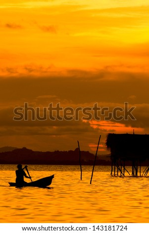 Silhouette local sea gypsies paddling a canoe during sunset near Mabul Island , Sabah - stock photo