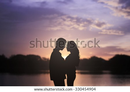 silhouette lover couple over natural backgrounds at the beach:black shadow loving people hug and try to kiss for show about their love:passion in love concept.valentines concept.image with vignette. - stock photo