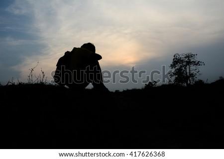 Silhouette man  desperate sunset background. - stock photo