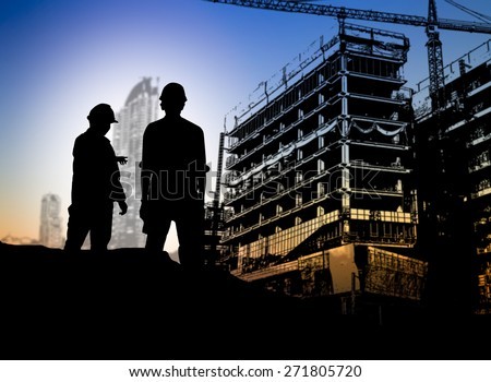 silhouette man engineer looking blueprint in a building site over Blurred construction site - stock photo