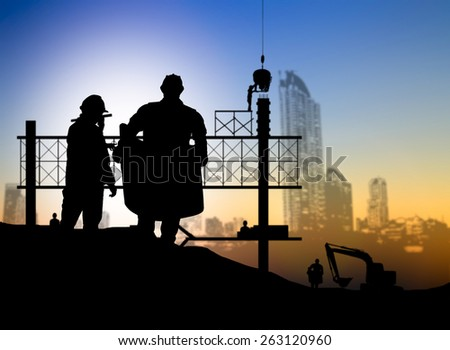 silhouette man engineer looking blueprint in a building site over Blurred construction worker on construction site