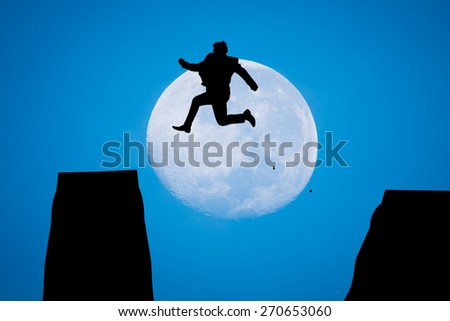 silhouette Man Jumping in sun rise with big moon - stock photo