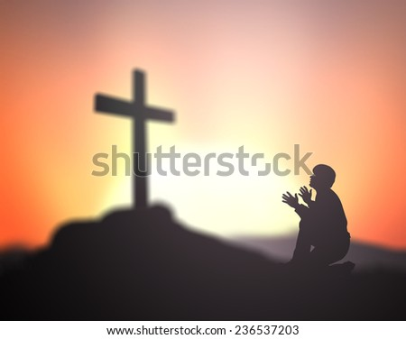 Silhouette man kneeling and raising hands over the cross on a sunset background. Worship, Forgiveness, Mercy, Humble, Evangelical, Reconcile, Adoration, Glorify, Redeemer, Redemption, Love concept.