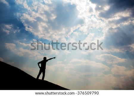 silhouette man on mountain top point to sky
