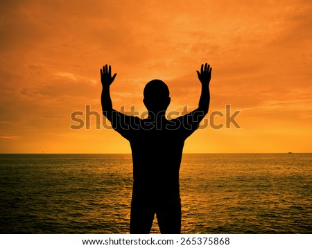 Silhouette man show two hands up in the air at sunset beach - stock photo