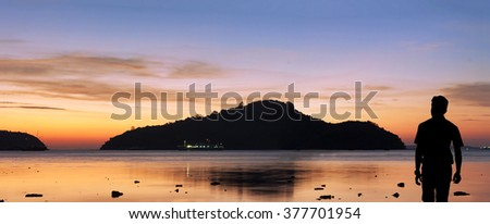 Silhouette man watch Twilight before sunrise at the beach, in Phuket, Thailand, Panorama Landscape. - stock photo