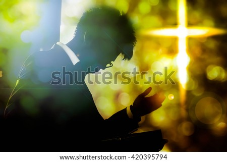 Silhouette man with cross on blurry background,Hope faith concept - stock photo