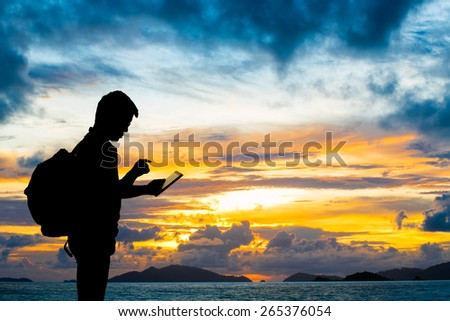 Silhouette man with digital tablet in hands at sunset beach