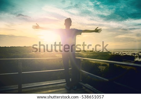 Silhouette man with hands rise up on beautiful view. Christian praise on hill thanksgiving day background. Man consumed by wanderlust nature standing open arms enjoying sun concept fun world wisdom