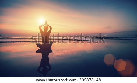 Silhouette meditation girl on the background of the sea and sunset. Yoga and healthy lifestyle. - stock photo