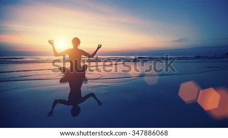 Silhouette meditation woman on the background of the sea and sunset. Yoga and healthy lifestyle.