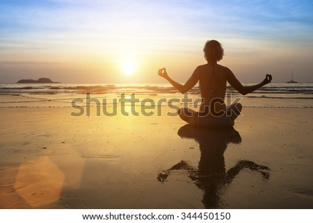 Silhouette meditation yoga girl on the background of the stunning sunset on the Sea. Healthy lifestyle.