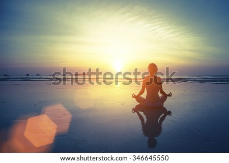 Silhouette meditation yoga woman on the background of the sea and amazing sunset. Healthy lifestyle. - stock photo