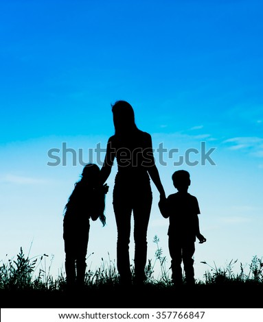 silhouette mother and children holding hands at sunset.