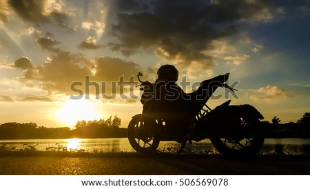 Silhouette motorbike beside the natural lake and beautiful sunset sky.
