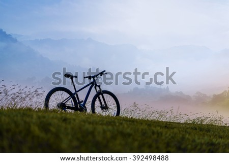 Silhouette Mountain Bike on beautiful landscape mountain and foggy - stock photo
