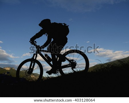 silhouette mountain biker - stock photo