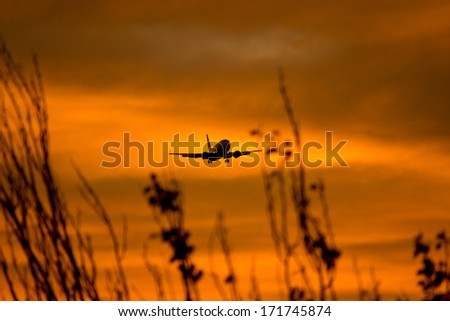 Silhouette of a aircraft approaching the airport. - stock photo