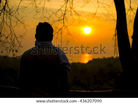 Silhouette of a backpacker begins the journey in the early morning by the river with golden sunshine and pine forest background - stock photo