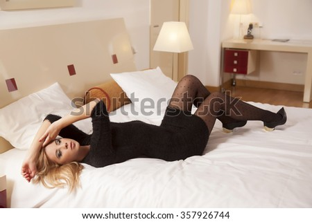 silhouette of a beautiful attractive and sexy young adult sensuality pretty blonde woman wearing elegance fashionable dress lying on the bed in bedroom - stock photo