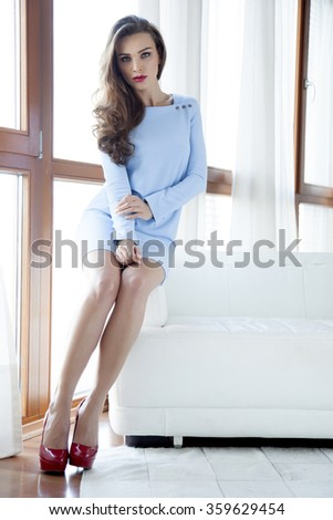 silhouette of a beautiful attractive sensuality and sexy young adult pretty brunette woman wearing elegance fashionable blue dress  sitting on white sofa on the window