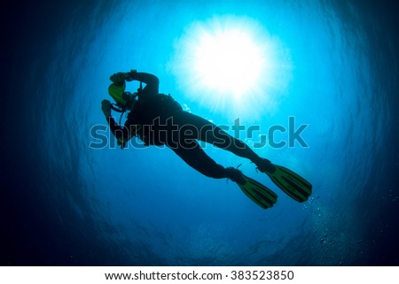 Silhouette of a beautiful female diver at shallow water- - stock photo