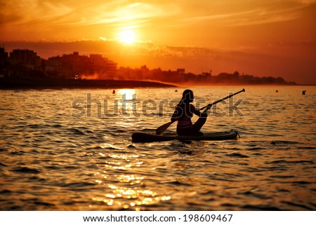 Silhouette of a beautiful girl floating at sea on paddle surf board encountering stunning sunrise reflected on the Gulf Indian Ocean