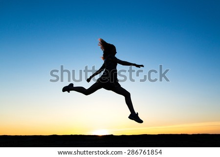 Silhouette of a beautiful happy healthy woman dancer in lights of sunrise