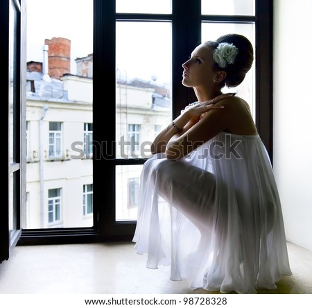 Silhouette of a beautiful thoughtful bride sitting on window sill - stock photo