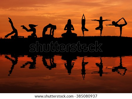 Silhouette of a beautiful Yoga woman at sunset with water reflection