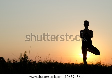 Silhouette of a beautiful Yoga woman in the morning - stock photo
