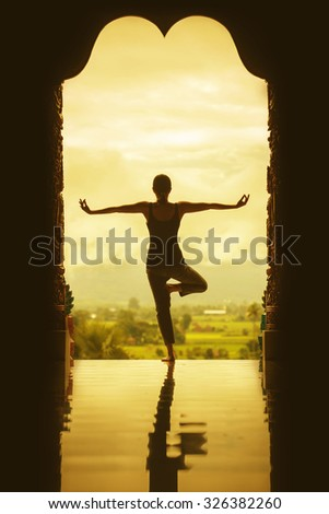 Silhouette of a beautiful Yoga woman in the morning - vintage style color effect - stock photo