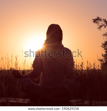 Silhouette of a beautiful Yoga woman on sunrise and rays of light surrounding her. Retro filter photo - stock photo