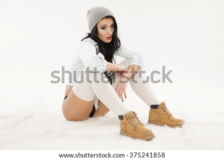 Silhouette of a beautiful young adult attractive sexy and sensuality pretty brunette woman in grey cab and socks, brown shoes and blue jeans shirt sitting on white background - stock photo
