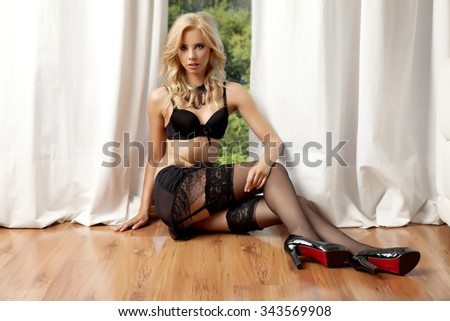 silhouette of a beautiful young adult slim sexy and attractive pretty blonde sensuality woman in black lingerie against the morning sunlight window in apartment - stock photo