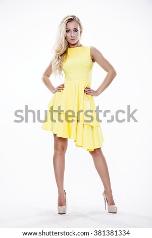 Silhouette of a beautiful young adult slim sexy and attractive sensuality pretty blonde woman in yellow elegance fashionable dress isolated on white background - stock photo