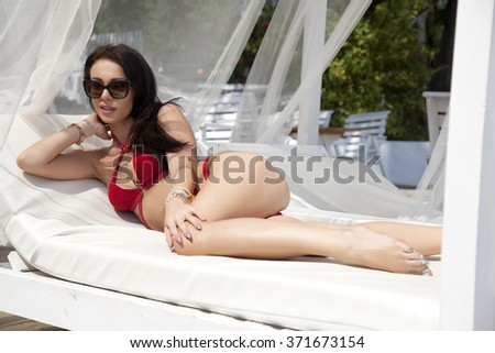 Silhouette of a beauty young adult attractive sexy and sensuality pretty brunette woman in red bikini lying on the summer sunlight beach