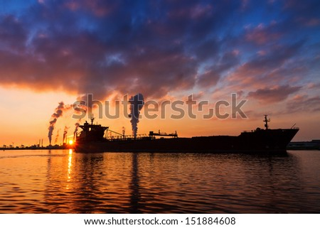 Silhouette of a big cargo ship and industry at sunset in IJmuiden in the Netherlands - stock photo