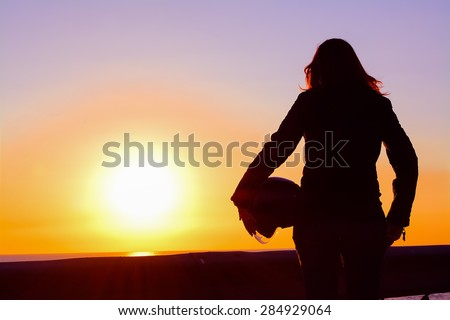 silhouette of a biker girl at sunset by the sea - stock photo