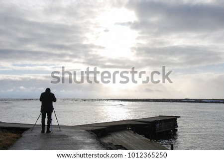 Silhouette of a birdwatcher on an old wooden pier by the coast of the swedish island Oland in the Baltic Sea