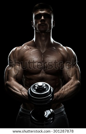 Silhouette of a bodybuilder. Power athletic man pumping up muscles with dumbbell. Confident young fitness man with core muscles, power hands and clenched fists. Dramatic light. - stock photo