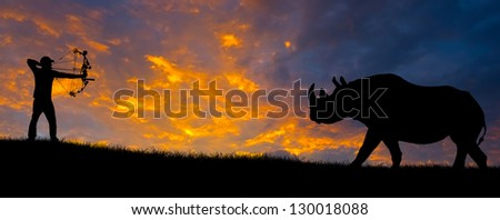 Silhouette of a bow hunter. - stock photo